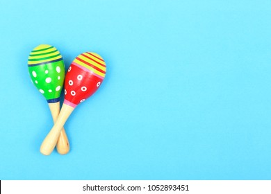 pair of colorful maracas on blue surface with copy space