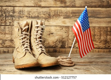 Pair of combat boots and USA flag on wooden background, close up