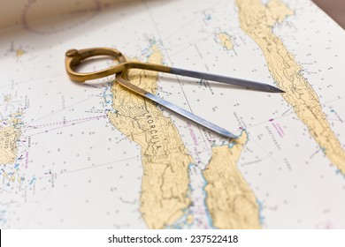 Pair of compasses for navigation on a sea map with low depth of field