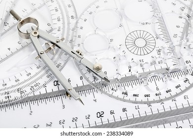 pair of compasses on transparent rulers and protractors