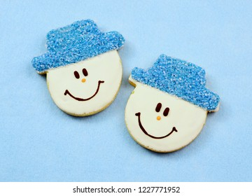 A pair of cookies decorated like cheerful snowmen with blue sparkle hats on a soft, blue felt background.