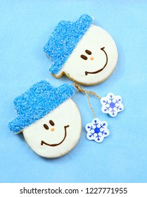 A pair of cookies decorated like cheerful snowmen with blue sparkle hats on a soft, blue felt background. Vertical composition
