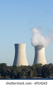 pair of cooling towers with one venting white smoke