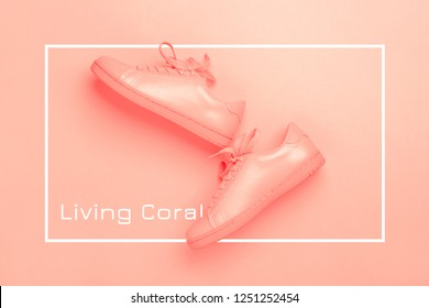 Pair of coral shoes on coral background. Trendy Living Coral color of the year 2019. Monochrome image.