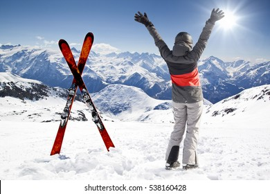 Pair of cross skis with woman skier, hands up