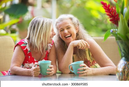 Pair of cute middle aged female friends laughing