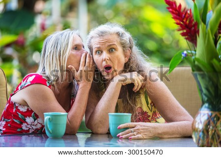 Pair of cute middle aged female friends whispering
