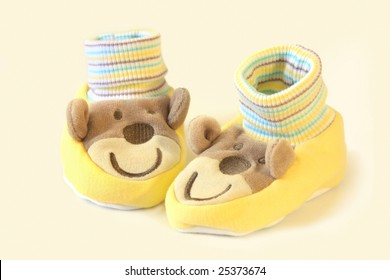 A pair of cute yellow baby socks or booties, with monkey faces.