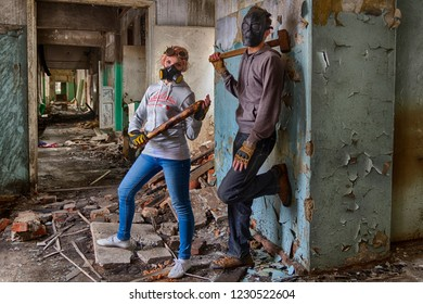 A pair of cyberpunk hooligans: a girl in respirator gas mask and steampunk goggles with a bat and a guy in skull mask with a sledgehammer, standing in the middle of the ruins of a building. Fighters