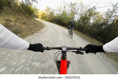 Pair of cyclist mountain biking in a forest in a winter day