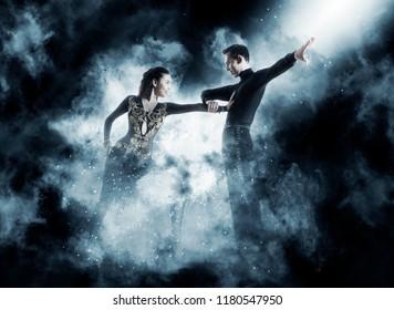 Pair of dancers dancing ballroom dark blue smoke background