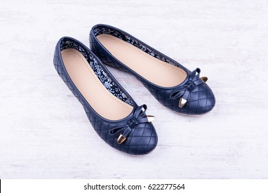 Pair of dark blue ladies' flat shoes on white wooden background.