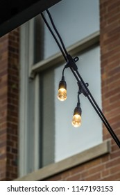Pair decorative white lights selectively focused against a soft window and brick wall