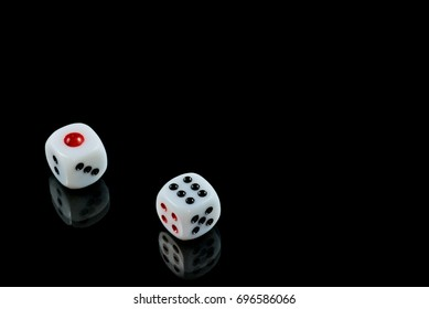 A pair of dice, on black, having rolled a lucky seven.