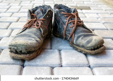 A pair of dirty boots. Old worn dark blue leather shoes with variegated brown laces. Background from gray pavers. The concept of poverty, homelessness, lack of money. Selective focus