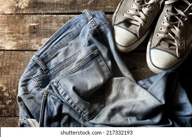 Pair of dirty jeans thrown on floor with a pair of sneakers