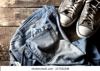 Pair of dirty jeans with twenty euro bill in the pocket thrown on floor with a pair of sneakers