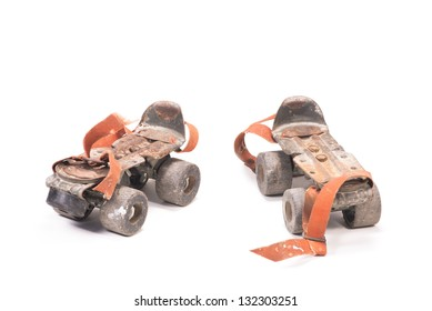 Pair of dirty rusty aged roller skates isolated over white