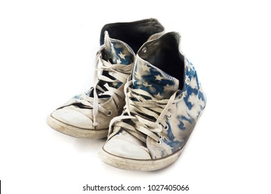 Pair of dirty sneakers on white background.