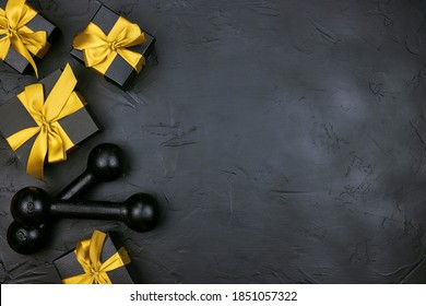 A pair of dumbbells and gifts with gold ribbons on a black background.  Holiday fitness sale or black friday concept. Top view with copy space.