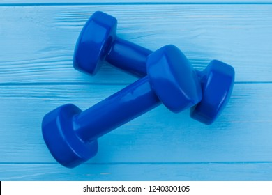 Pair of dumbbells on color background. Colourful hand weight dumbbells in a crossed position on blue wooden boards. Equipment for fitness workout.