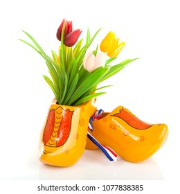 Pair of Dutch wooden shoes with tulips over white background
