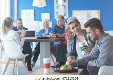 Pair of employees having a lunch break, and a coffee