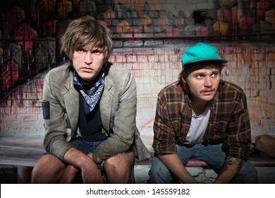 Pair of European homeless youth sitting on bench