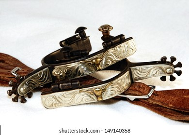 A pair of fancy, engraved western spurs with spur leathers in a high contrast white environment (shallow focus on upper spur).