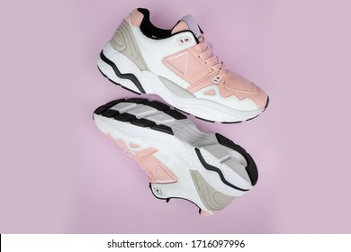 Pair of fashion colorful sneaker shoe on a pink isolated background Fitness sneakers shoes for training, running shoe. Sport shoes. Fashion pink sneaker, daddy shoe, ugly shoe, street fashion.
