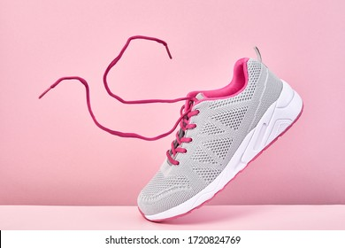 Pair of fashion stylish sneakers with flying laces, Running sports shoes on pink background