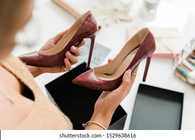 Pair of fashionable leather high-heeled shoes held by young female shopper over open black box