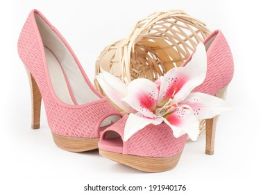 pair of fashionable pink high-heeled female shoes with lily and basket isolated over white