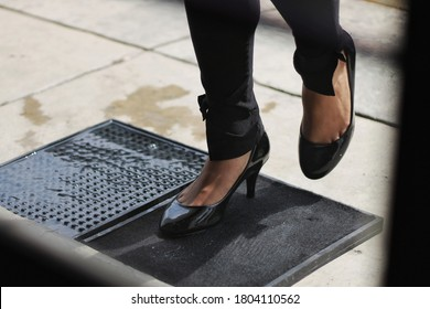 A pair of feet with heels are disinfected with a disinfectant mat before the person get inside a shop