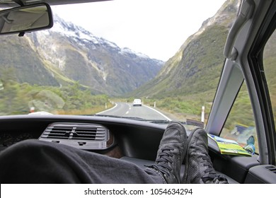 A pair of feet, resting on the dashboard of a car with the amazing landscape views of the impressive mountains on the highway towards Milford Sounds, New Zealand. A concept of travelling by camper car