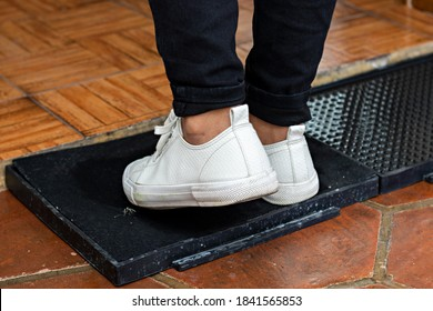 A pair of feet with sneakers are disinfected with a disinfectant mat before the person get inside a house