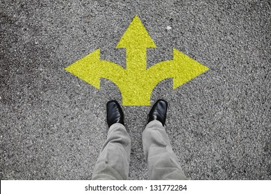 A pair of feet standing on a tarmac road with yellow arrow print pointing in three different directions for the concept of making decision at the crossroad.