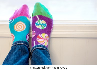 A pair of feet wearing brightly colored odd socks