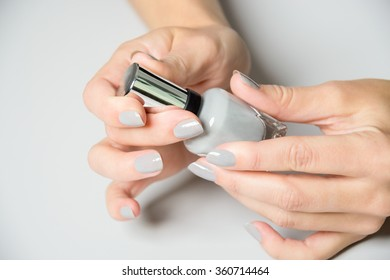 Pair of female hands opening nail polish bottle