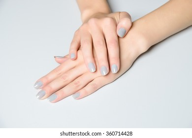 Pair of female manicured hands on white table