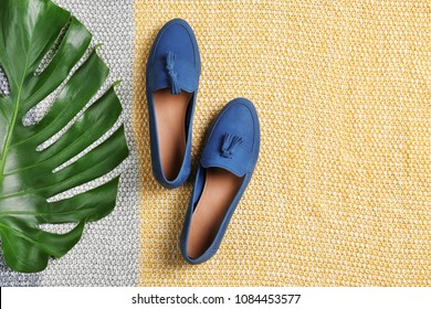Pair of female shoes with green leaf on fabric, top view