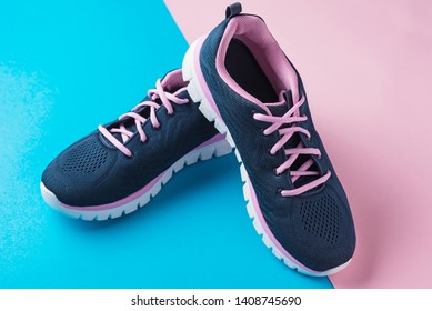 Pair of female sport shoes on pink and blue background