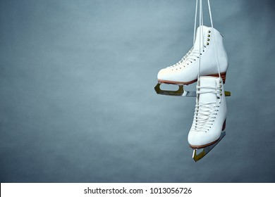 A pair of female white skates on a gray background.