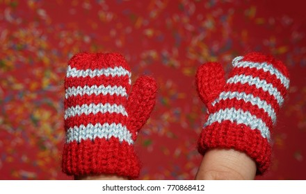 Pair of fingers of hand wear little knitted woolen red stripped mittens for children isolated on colorful red background