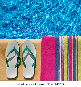 Pair of flip flop thongs and a towel on the side of a swimming pool