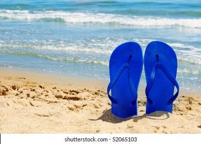 a pair of flip-flops stuck on the sand of a beach