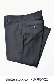 A pair of folded dress slacks on a white background