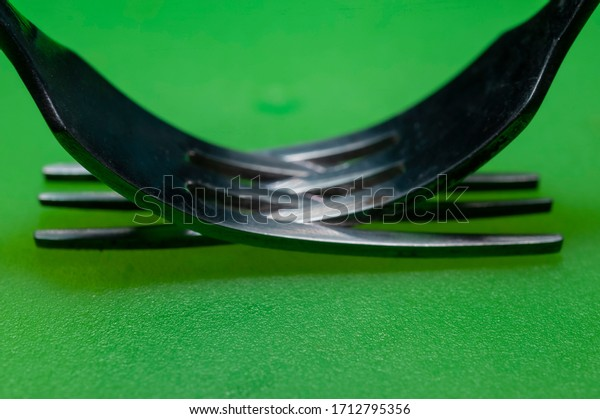 A pair of forks bonded close up view on green table