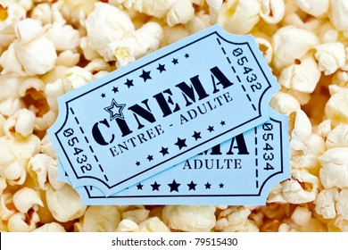 Pair of french cinema tickets on popcorn background