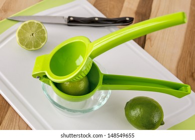 A pair of fresh limes ready for juicing with a manual juicer.